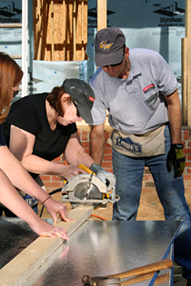 Lynn Burris, an executive assistant for Facilities, learns to use a circular saw with a hand from Tom Skolnicki of the University Architect's office and Rachel Patrick from Capital Projects Management.