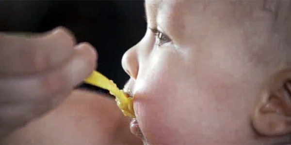 A baby eating baby food.