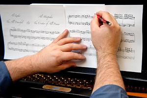 Scearce's hands on a musical score.