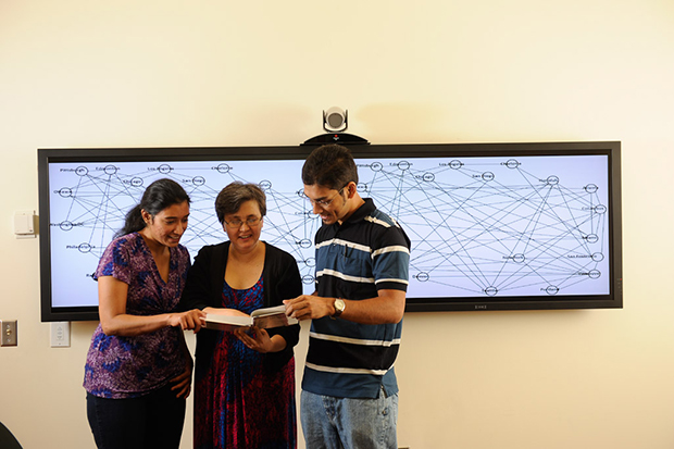 Computer science Ph.D. student Kanchana Padmanabahn, professor Nagiza Samatova and Ph.D. student Arpan Chakraborty (left to right) read a data mining textbook they co-edited.