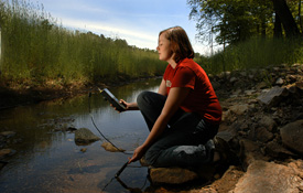 Student testing water at a stream.