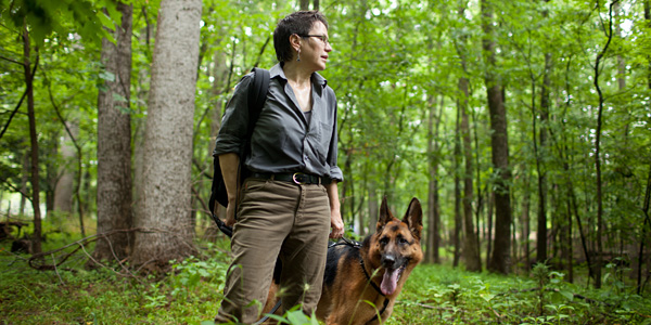 woman standing in woods with dog