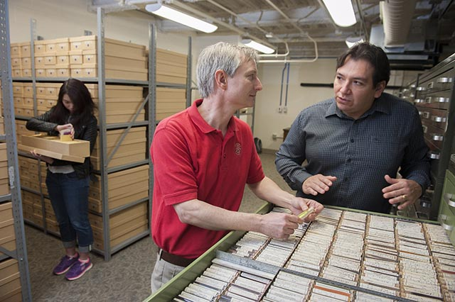 Textile chemist David Hinks (left), director of the emerging Forensic Sciences Institute, and analytical chemist Nelson Vinueza (right) inspect samples from the Max A. Weaver Dye Library.