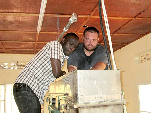 NC State junior Tyson Huffman (right) and a team member repair equipment at a facility producing sanitary pads in Rwanda.