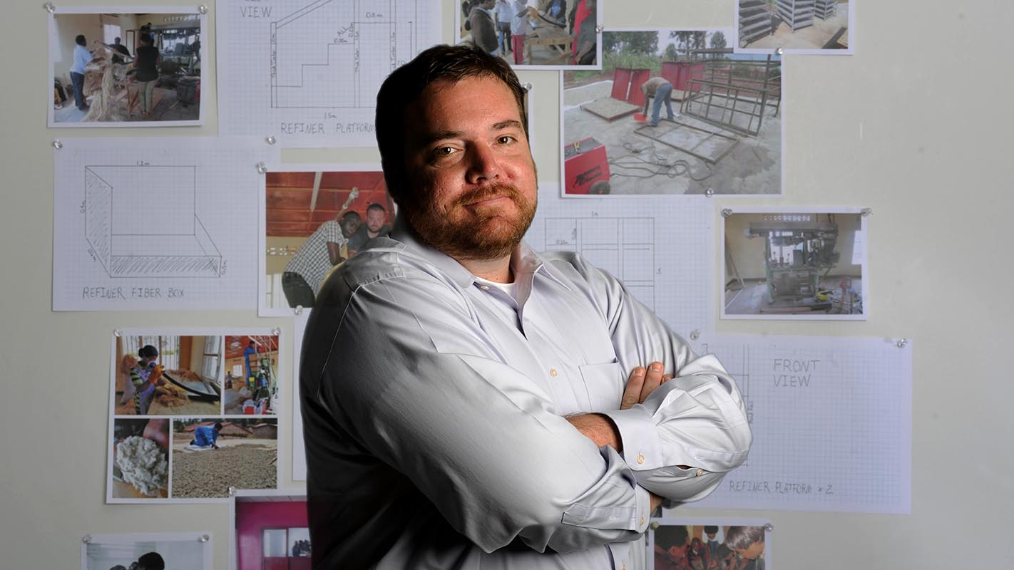 NC State student Tyson Huffman stands in front of a board showing construction plans.