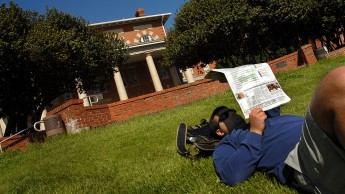 College of Education junior Greg Capobianco reads Technician while lying on the grass in front of the 1911 building.
