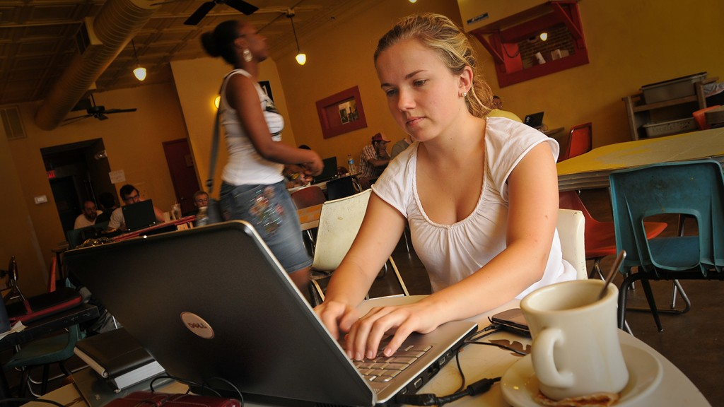Student at coffee shop on laptop.