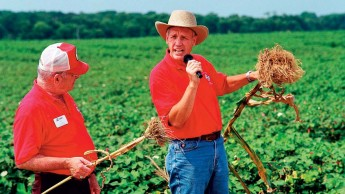 Ron Heiniger holding a microphone as he explains farming to an audience in a field.