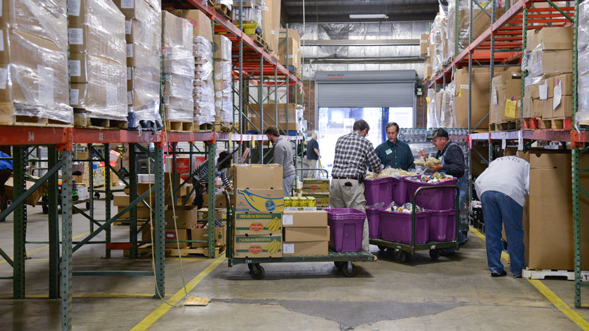 Buyers at the Food Bank of Central and Eastern North Carolina sort food in an aisle of the Raleigh branch.