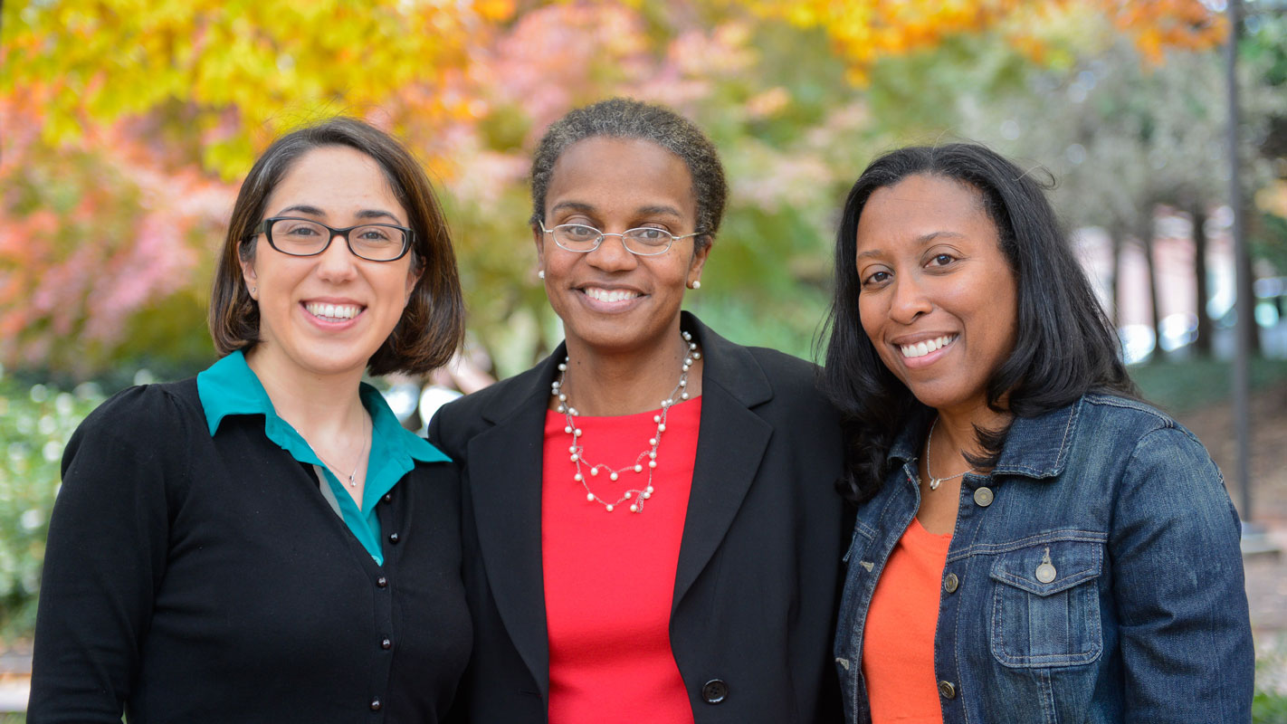 Three NC State industrial and systems engineers stand side by side in a garden on campus.