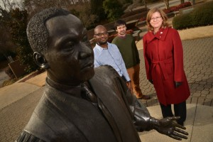 Researchers from NC State's  Virtual MLK project stand behind a statue of the man that inspired it.