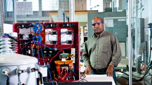 Hulgize Kassa, lab manager at NC State's FREEDM Systems Center, stands next to a transformer.