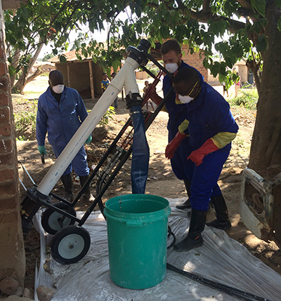Rogers, (in rear, holding the equipment) field-tested the Excrevator with collaborators in Malawi. Photo courtesy of Tate Rogers.