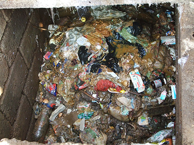 Pit latrines can be filled with solid trash (like this one in South Africa), which can clog the Excrevator. Photo courtesy of Tate Rogers.