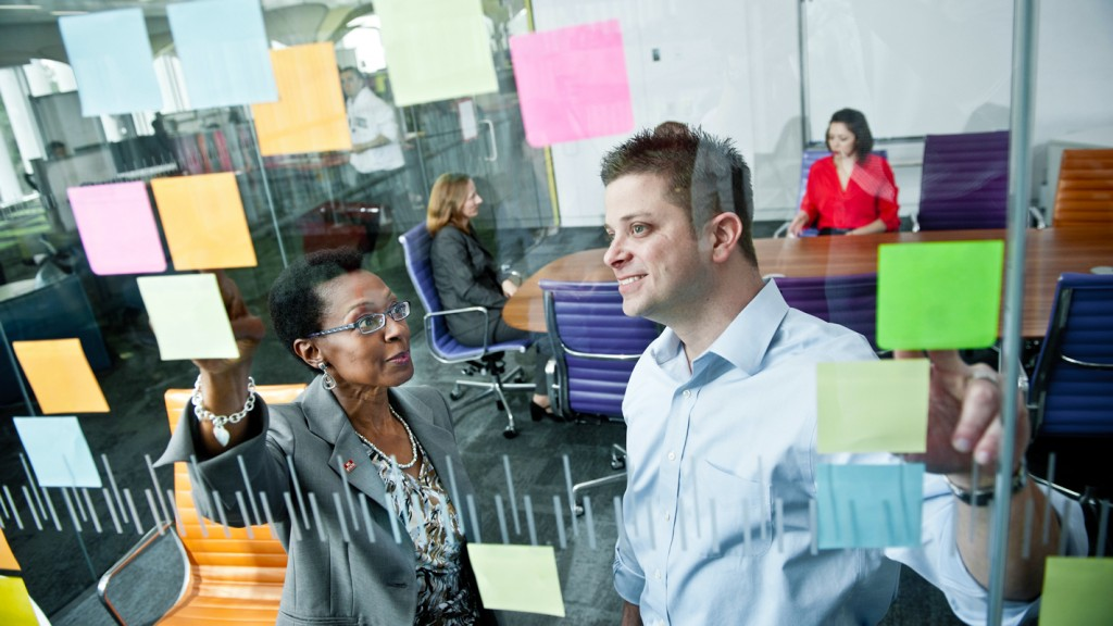 A white man and a black woman smiling behind a glass wall adorned with post-it notes.