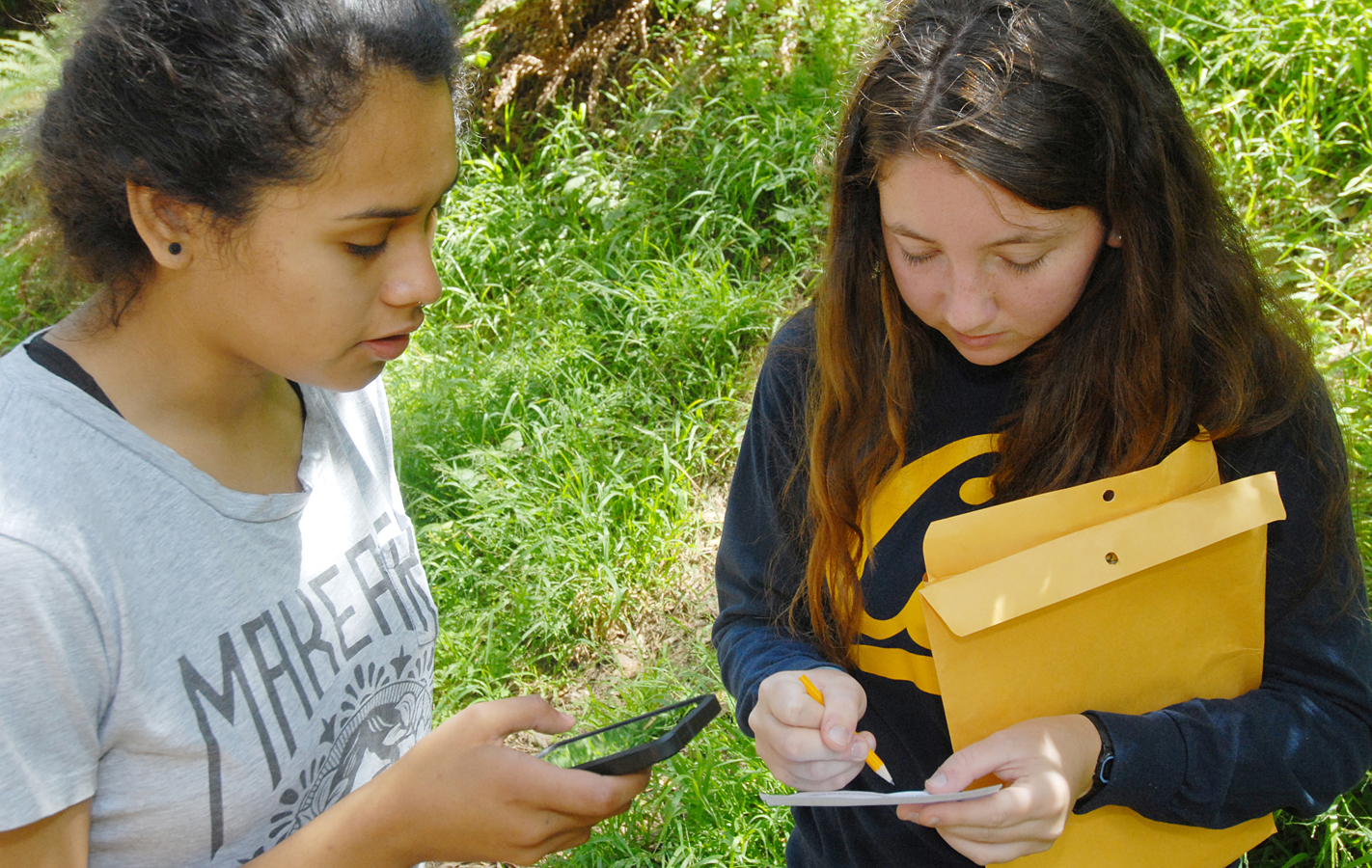 Two women collect data using a mobile app