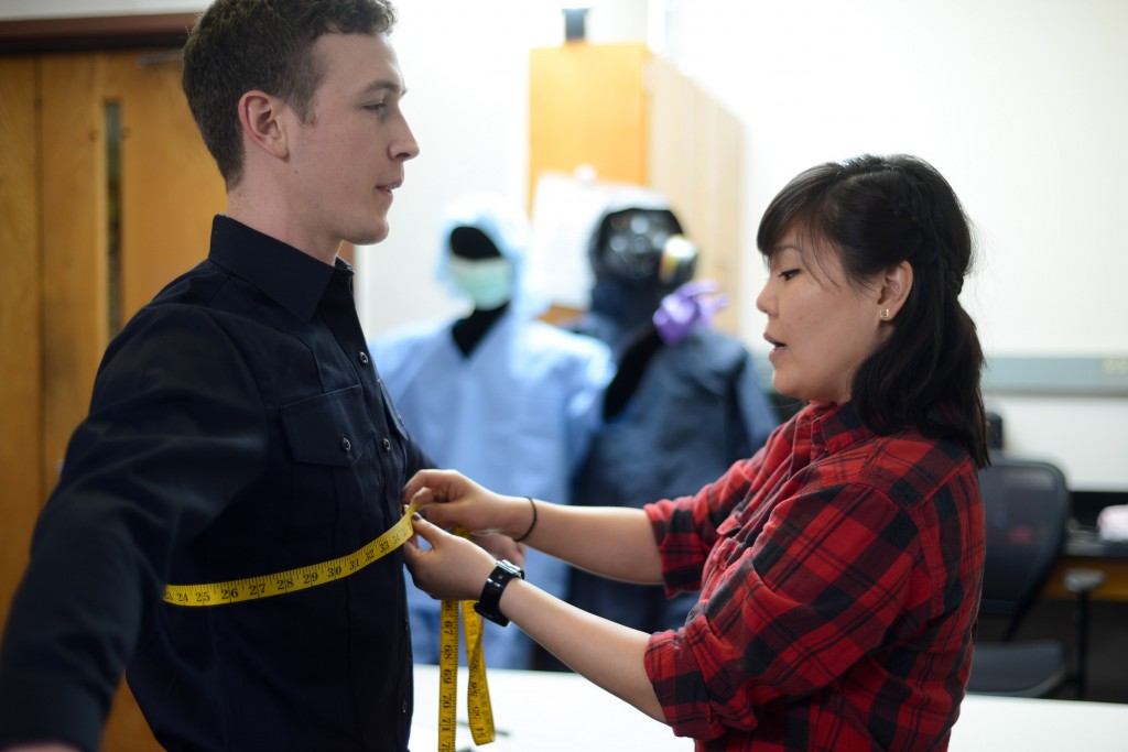 Researcher measures uniform shirt's fit on doctoral student