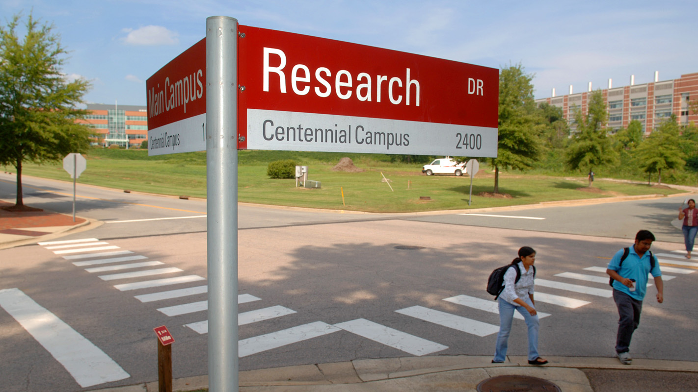 Street sign on Centennial Campus with students walking.