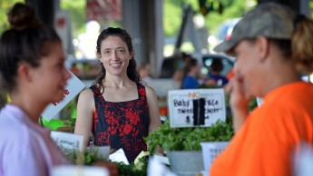 A woman listens in on a conversation between two merchants at the North Carolina famers market.