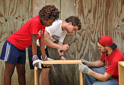 Students spend spring break on a service-learning trip to Belize. Amanda McKnight (left) and Darren Lipman (right) hold boards in place as Joey Brown hammers.