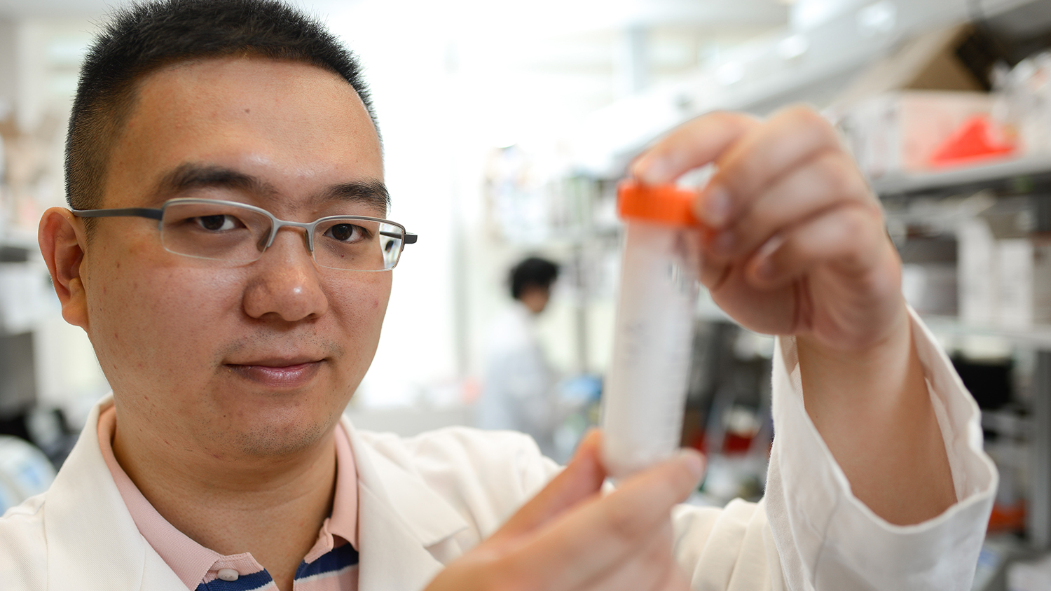 Zhen Gu holds up a solution in his lab on NC State's Centennial Campus.