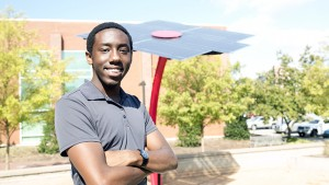 NC State computer science graduate Xavier Primus stands in front of a 16-foot solar sculpture.