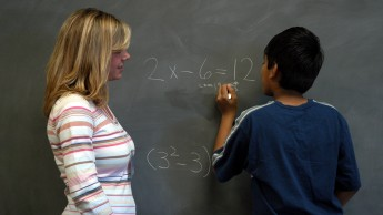 Teacher with student at blackboard
