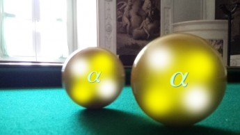 The scattering of two alpha particles is illustrated. This antique English billiards table is located in a late 18th century villa called Villa Tambosi in Trento, which houses the European Centre for Theoretical Studies in Nuclear Physics and Related Areas.