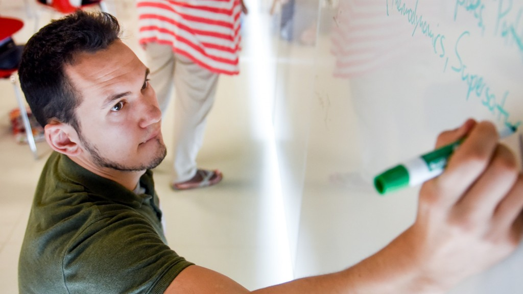 A man in a green shirt writes on a whiteboard at NC State's Dissertation Institute.