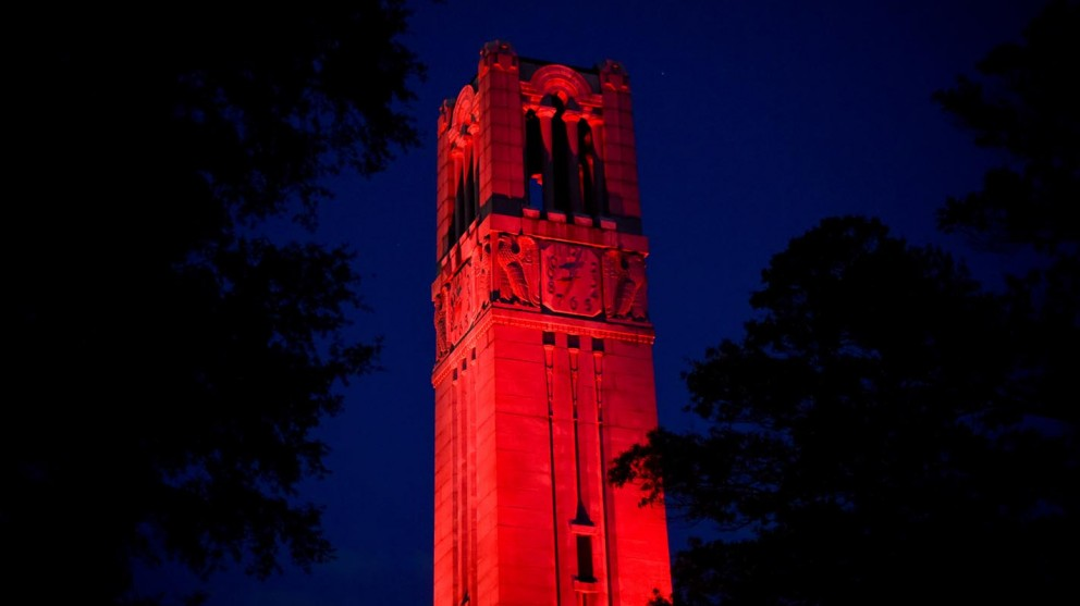 The Memorial Belltower at NC State lit in red to celebrate faculty excellence.