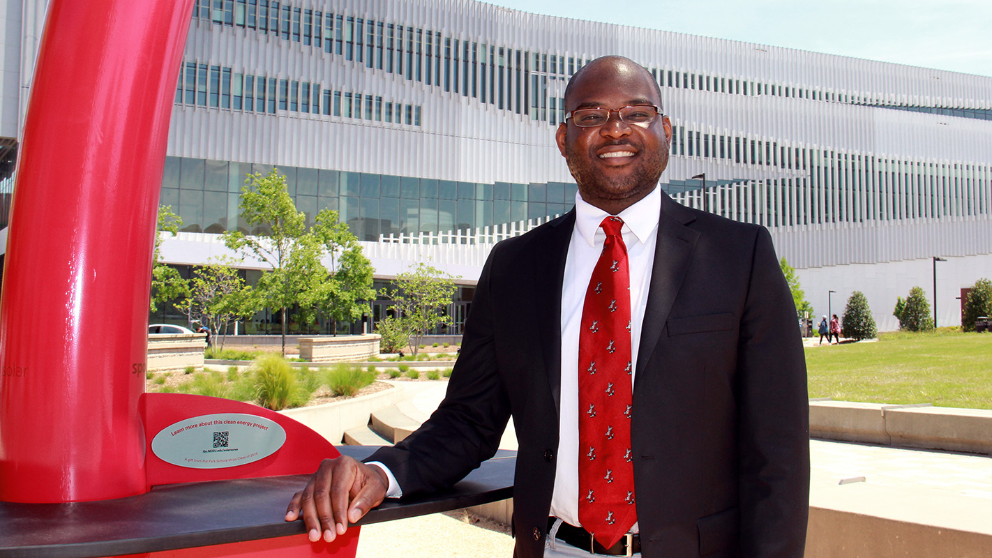 Keon Pettiway, Ph.D. in rhetoric, communication and digital media, stands by the solar sculpture in front of NCState's Hunt Library.