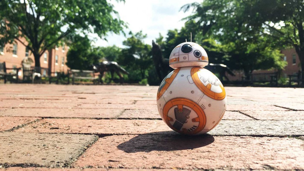 A brave toy droid rolls alone in front of the wolves at NC State's Wolf Plaza.
