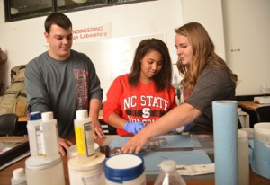 College of Textiles seniors Jamie McLain (left), Desirae Scruggs and Shannon Tart (right) work on the next generation of Gryppers.