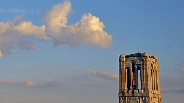 The top of the NC State Memorial Bell Tower peeks into view amid blue sky and clouds.