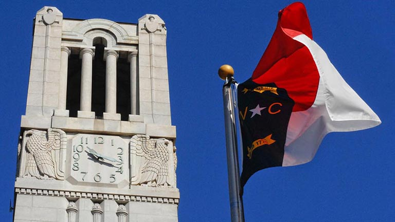 The NC State Memorial Bell Tower and the North Carolina state flag.
