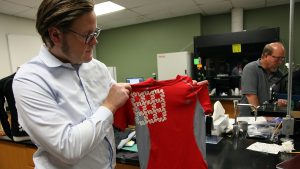 A man in a research lab holds up a red wearable tech T-shirt.