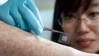 A researcher applies an insulin patch to a freckled forearm.