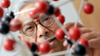 An NC State professor in materials science and engineering half-hidden behind a 3-D molecule.