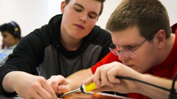 Two Catalyst program students work on soldering a circuit.