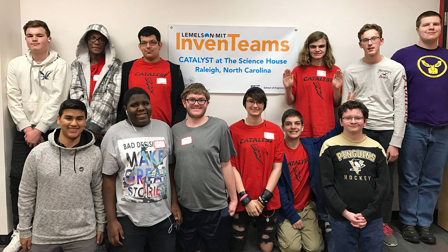 A group shot of the Catalyst InvenTeam in front of the banner bearing their name.