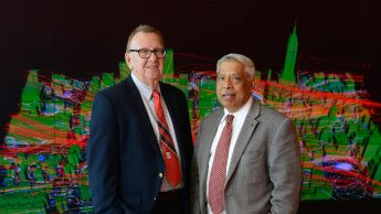 Two engineers professors pose together in front of a visualization wall at the Hunt Library.