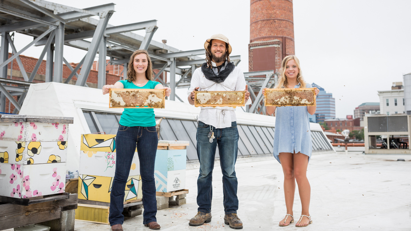 The staff of Bee Downtown poses with bees.