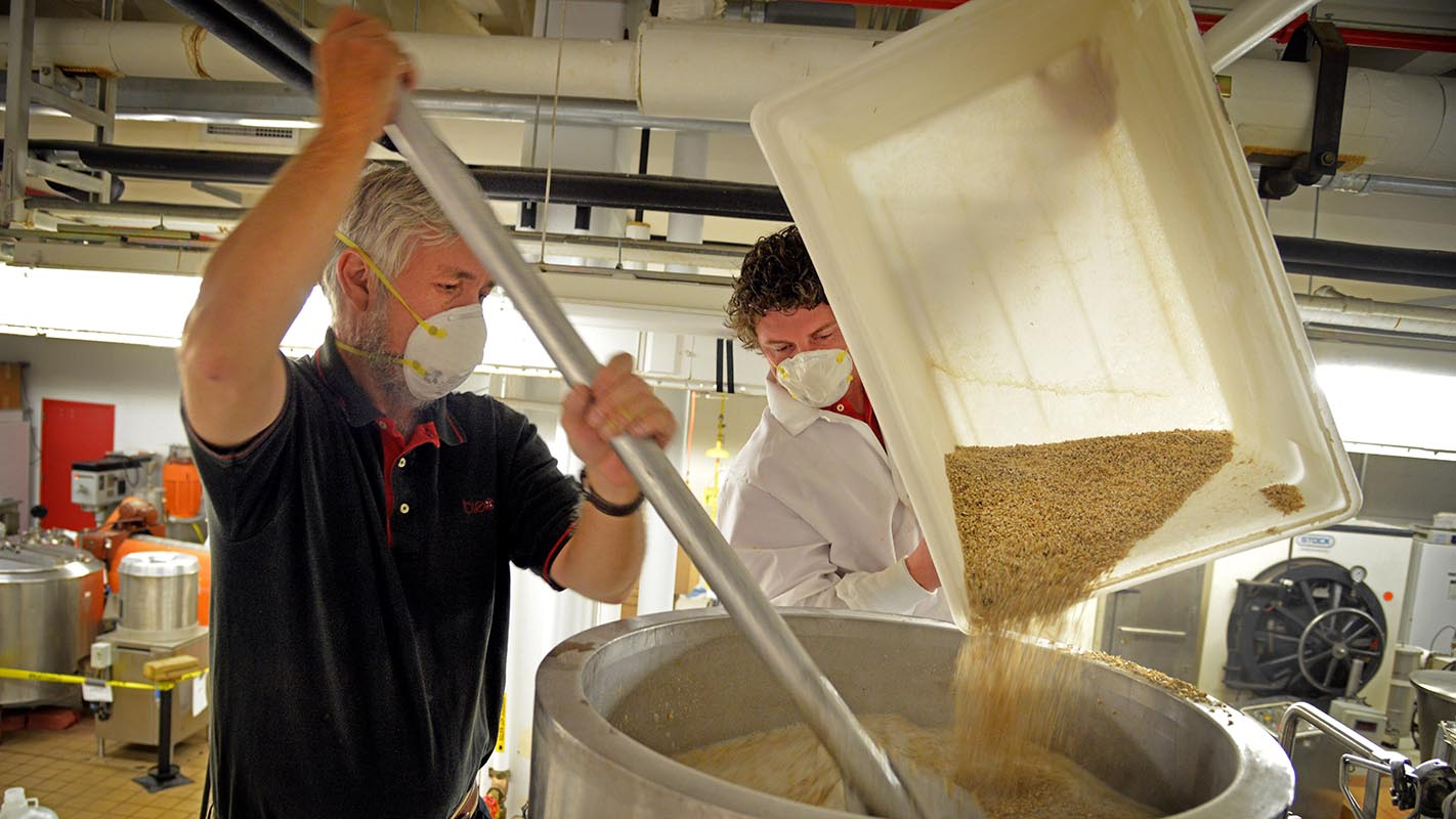 Dr. John Sheppard, coordinator for the undergraduate Bioprocessing Science Program, stirs malt while student Brandon Jackson (right) pours in the brewing lab at Schaub Hall.