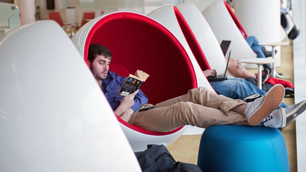 An NC State student lounges in a Ball Chair at the Hunt Library.