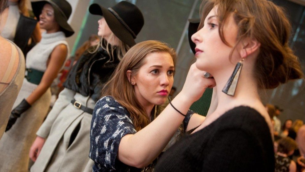 A student designer attends to a model backstage at Art2Wear 2015.