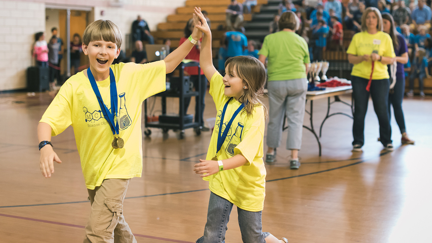 Two Science Olympiad participants high-five