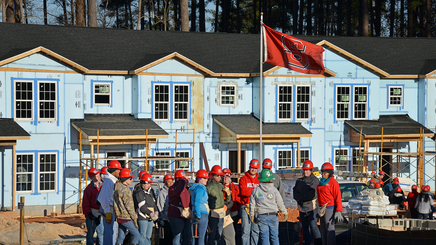 A group of Build-A-Block volunteers in hard hats gathered under an NC State flag.