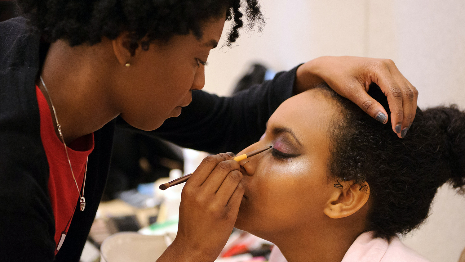 A makeup artist applies her craft to a student model.