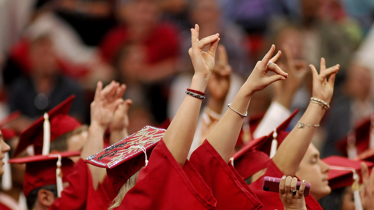 Newly minted NC State graduates throw up their wolf signs at Spring Commencement 2016.