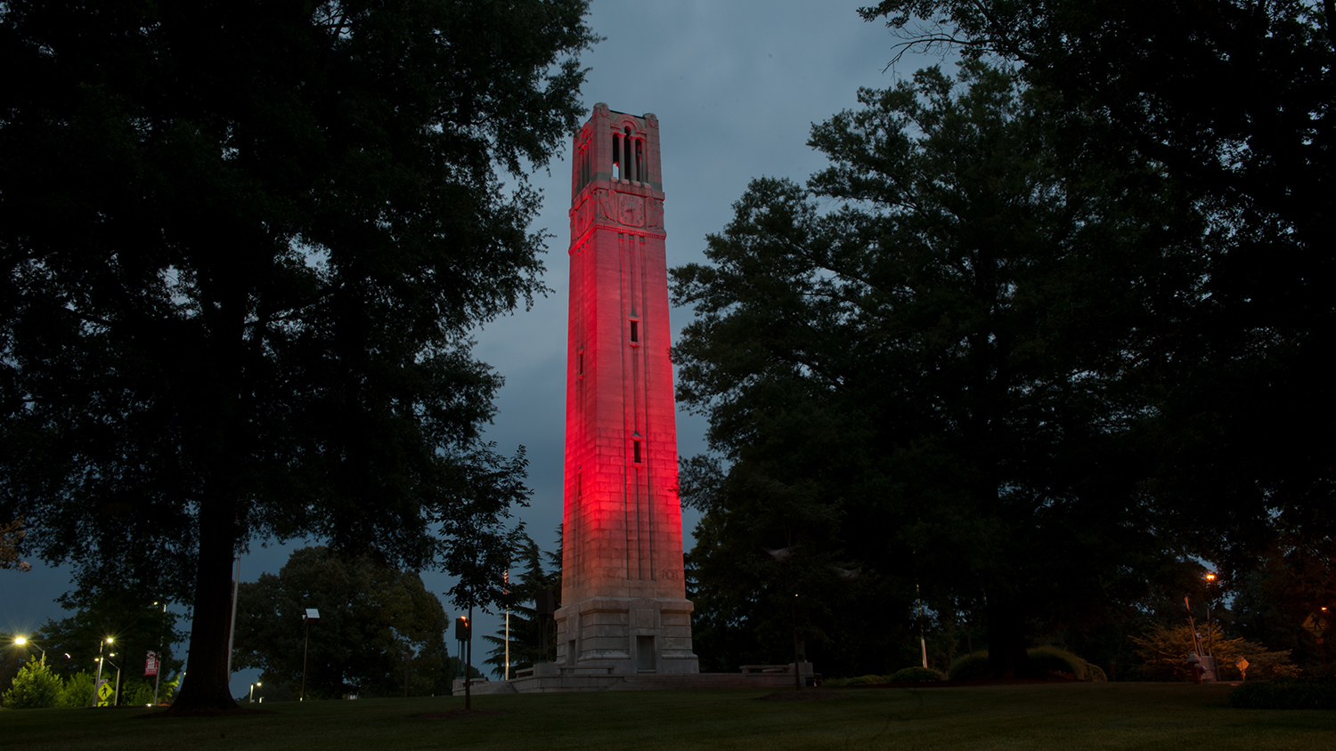 NC State Belltower lit from below with red lighting.